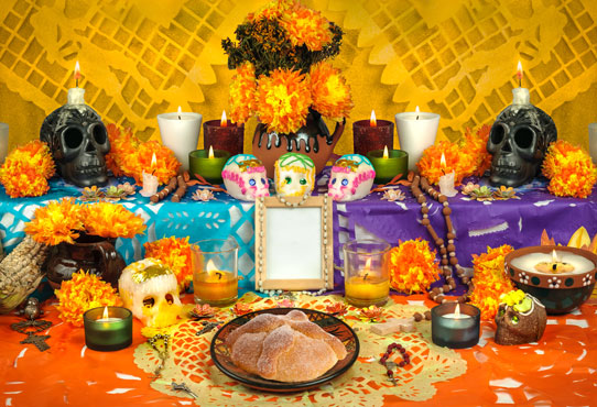 Traditional Mexican Day of the Dead altar with sugar skulls, candles and swwet round bread, pan de muerto